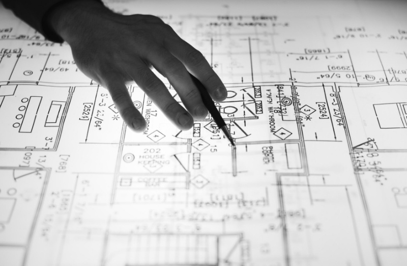 Main sur un plan de chantier
